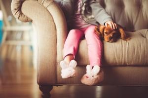 On näha väikese tüdruku jalgu, kes istub diivanil ja tema kõrval lamab väike koer. Tüdruk teeb koerale pai.