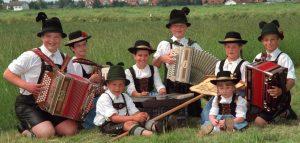 saksa rahvamuusikud koos instrumentidega istumas rohelisel aasal