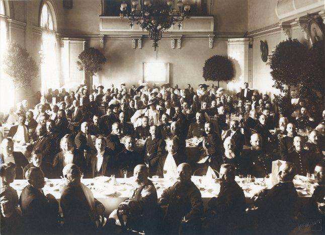 kroonlühtriga suures saalis istuvad kaetud pidulaudade taga pidulikult riides härrad ja prouad
