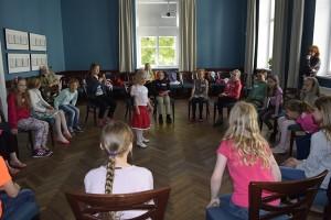 lapsed istuvad toolidel ringis suures saalis