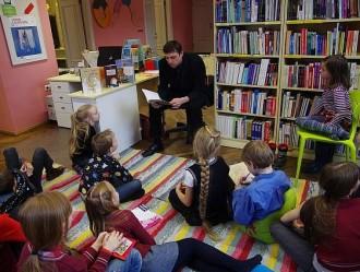 lapsed istuvad värvilisel triibulisel vaibal ja kuulvad kuidas neile üks mees raamatut ette loeb