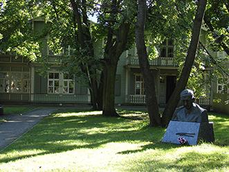 täislehtes puude vahelt paistab Kalamaja raamatukogu