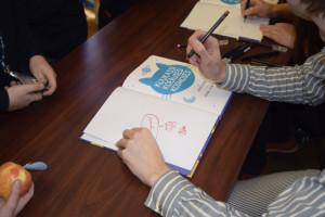 Joonas Sildre kirjutab autogrammi raamatusse