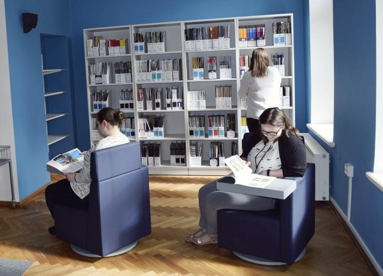 kahes mugavas lugemistoolis istuvad naised ja loevad, eemal suure raamaturiiuli juures otsib üks inimene raamatut