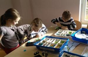 kaks tüdrukut ja üks poiss istuvad laua taga ja panevad kokku legoroboteid