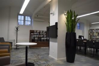 ümmargune laud seinale kinnitatud televiisori ees ja taamal on ajakirjade riiul ning lauad ajalehelugejatele või oma arvutiga töötajatele