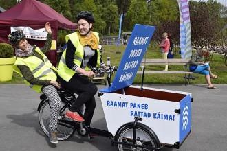 turvavestiga naine juhib suure raamatute vedamiseks mõeldud kastiga jalgratast