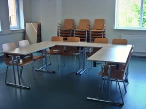 suurte akendega suur ruum laudade ja toolidega