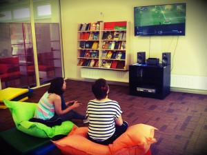 noored istuvad kott-toolidel ja mängivad videomängu