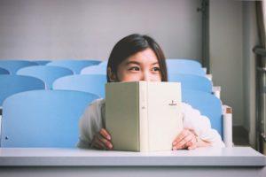 tüdruk istub ja hoiab käes avatud raamatut, mille ülmise äära üle ta piilub