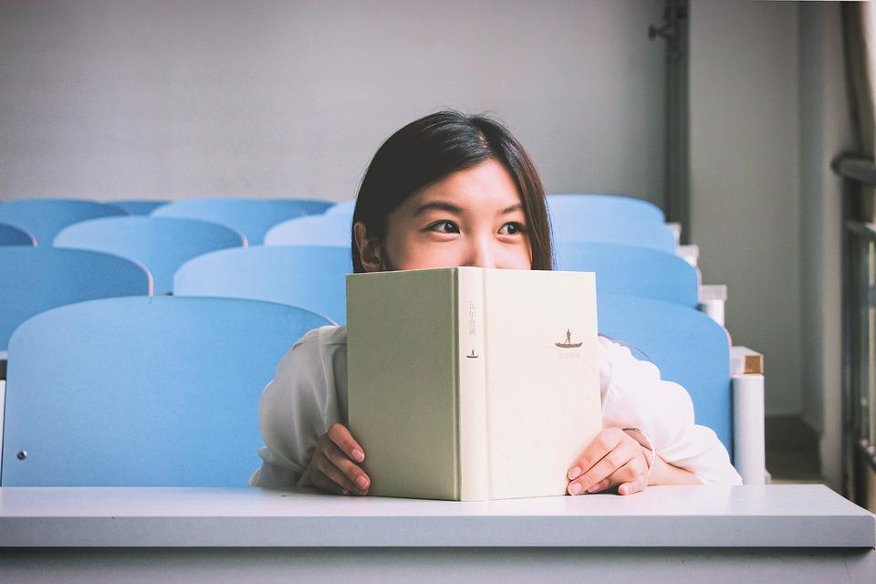 neiu istub ja piilub üle avatud ja näo ette tõstetud raamatu