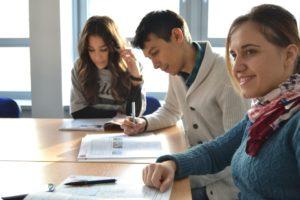 kaks noort naist ja üks noormees istuvad laua taga ja neil on ees avatud õpikud