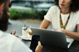 naine ja mees istuvad laua taga, naine vaatab midagi sülearvutist ja mees mobiilist