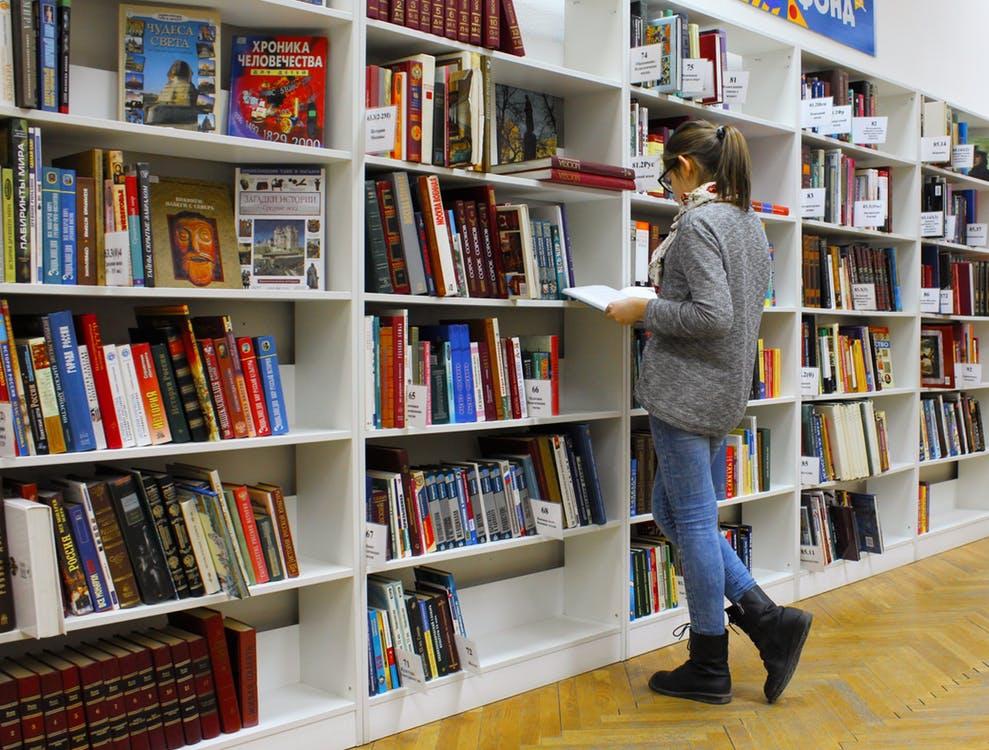 noor naine seisab suure raamaturiiuli ees avatud raamat käes