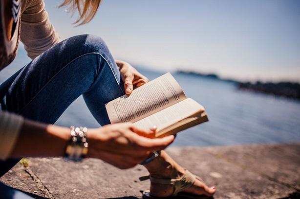 päikselisel suvepäeval loeb naine merelahe ääres kivist rinnatisel istudes raamatut