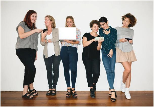 rõõmsad naised seisavad reas ja vaatavad oma nutiseadmete ekraane