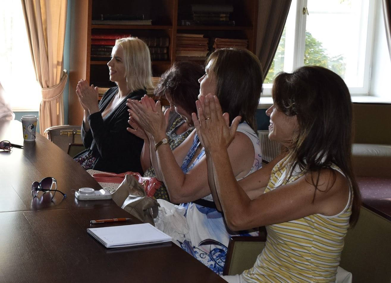 neli lauaääres istuvat ja rõõmsalt plaksutavat erinevas vanuses naist